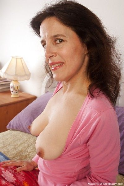 Seductive mature babe exposing her flabby tits and unshaven twat