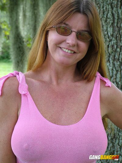 Mature amateur redhead Dee Delmar flashes big tits & naked upskirt outdoors