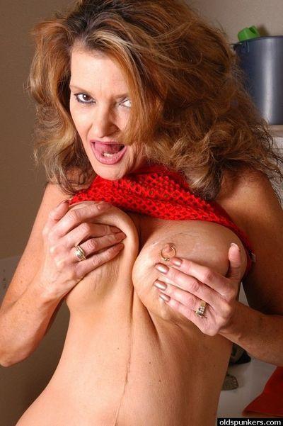 Curvy older blond Raven exposing huge tits and pierced nipples