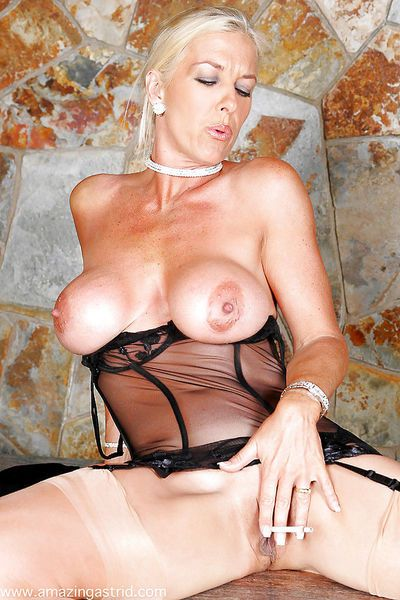 Big busted mature wench in girdle teases her gash while smoking a cigarette