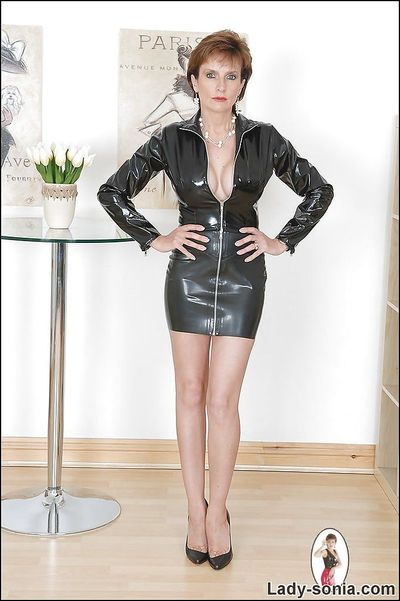 Leggy mature fetish lady in tiny latex dress uncovering her big jugs