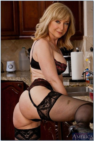 Busty mature seductress Nina Hartley posing in stockings and lingerie