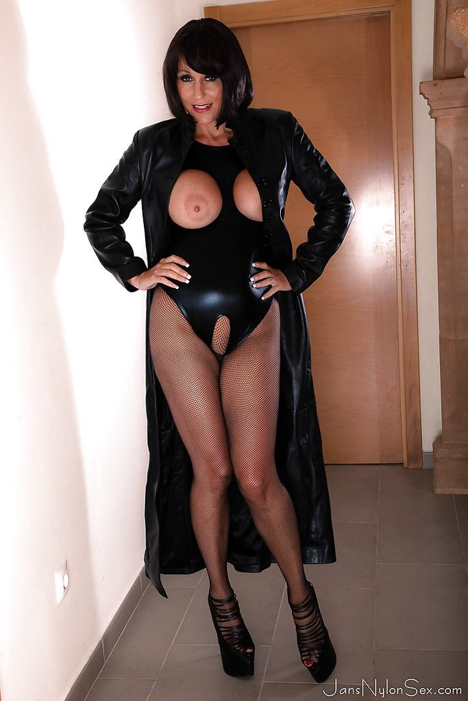 Busty European lady Jan Burton flashing big tits under leather coat