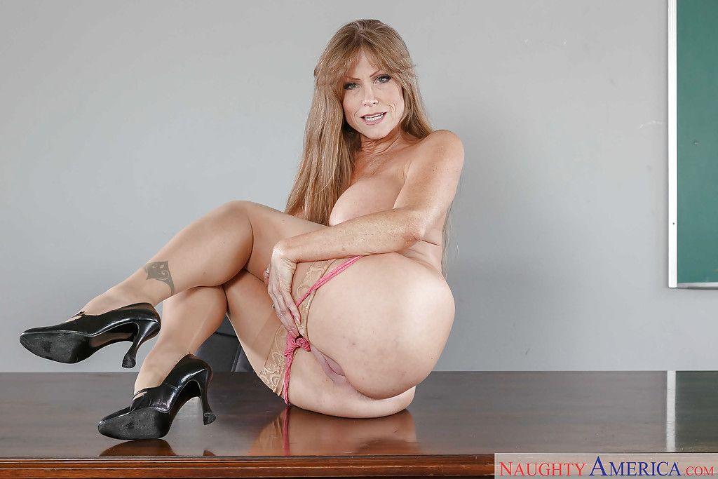 Mature pornstar Darla Crane exposing big tits in tan nylons on teachers desk