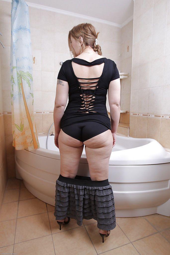 Tattooed mature Dana Karnevali reveals her hairy pussy in high heels