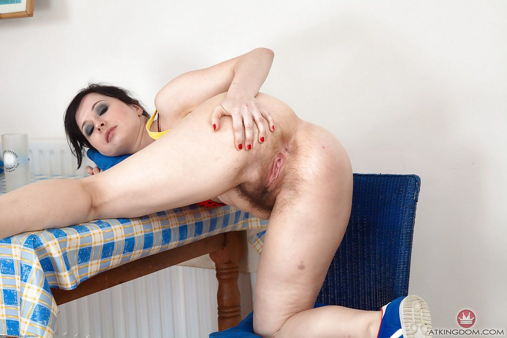 Mature broad Nikita climbing aboard kitchen table to exhibit her hairy vagina