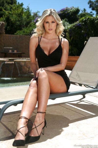 Blonde pornstar sheds short black dress to pose naked outdoors