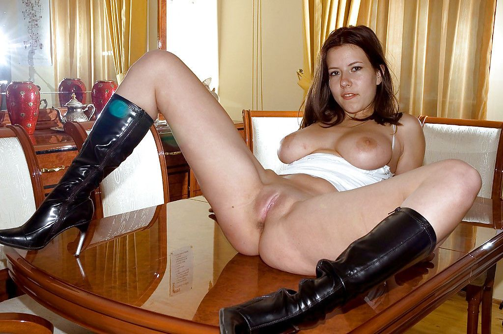 Busty brunette babe in boots stripping and spreading her legs