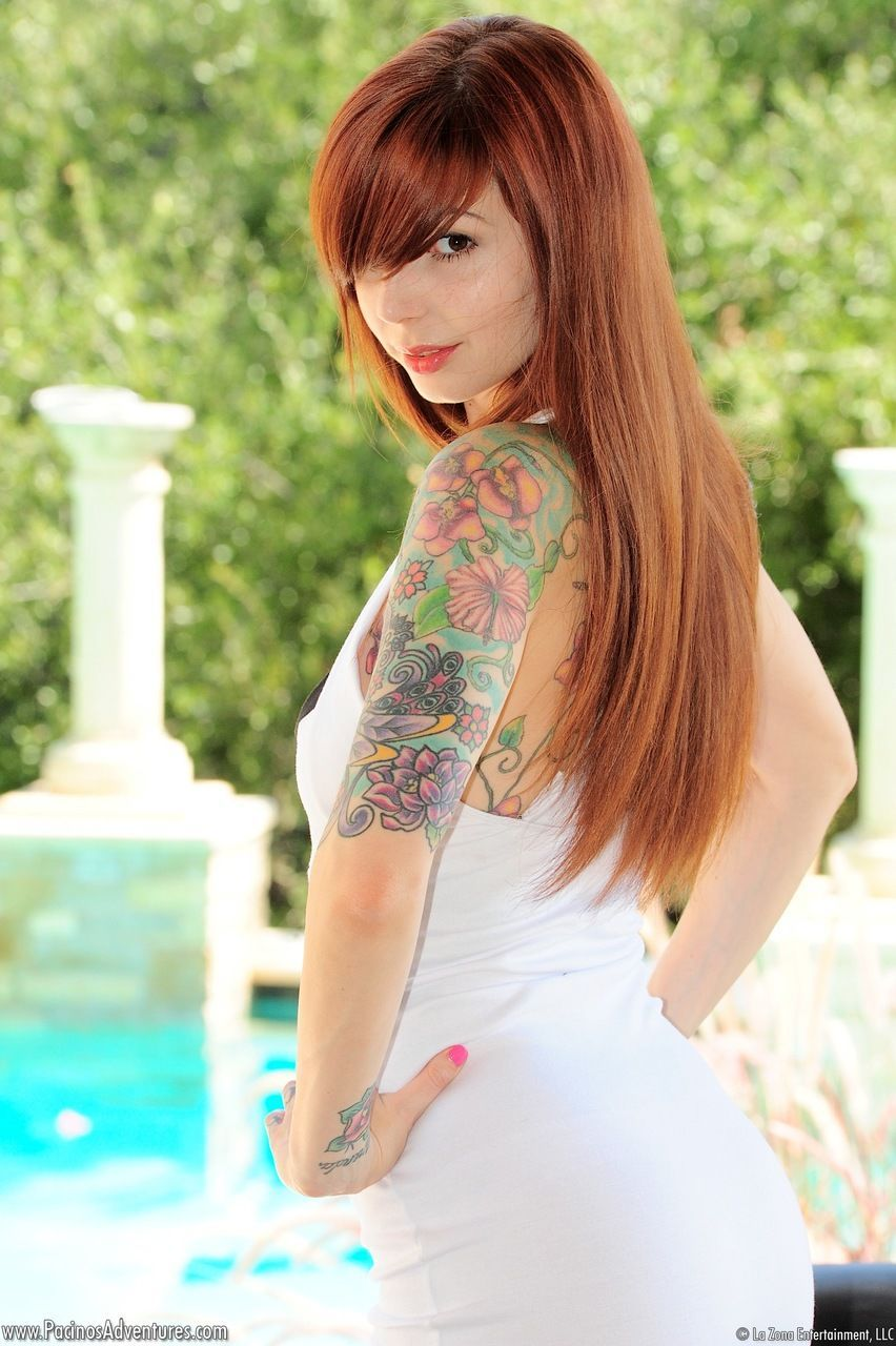 Tattooed redhead Ivy Snow casually removes her white dress to model naked