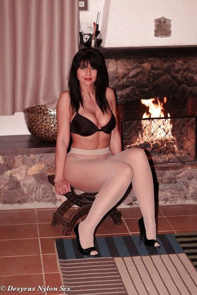Brunette nylon model Desyra Noir posing non nude beside fireplace