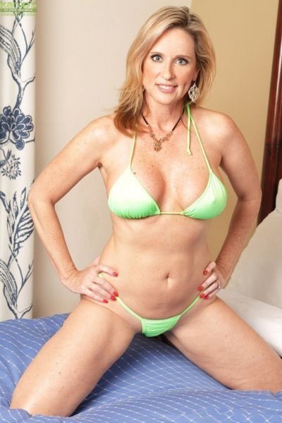Older amateur Jodi West removes her bikini before toying her pussy on bed