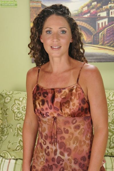 Curly-haired mature lady undressing and vibing her pierced clit