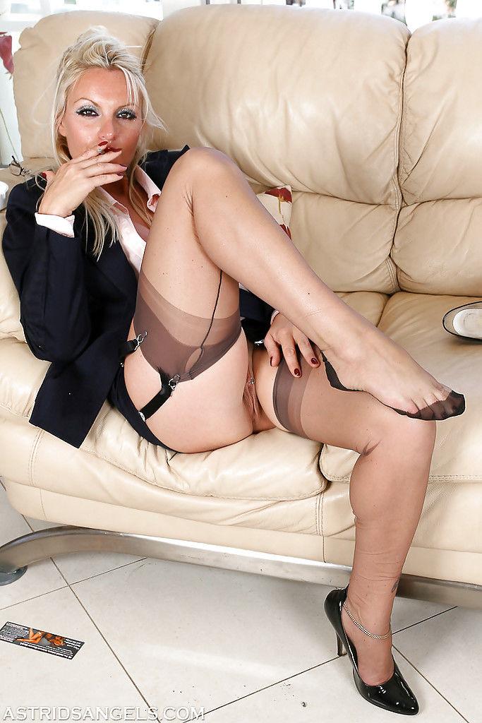 Curvy blonde lady in pantyhose flashing thigh and garters while smoking