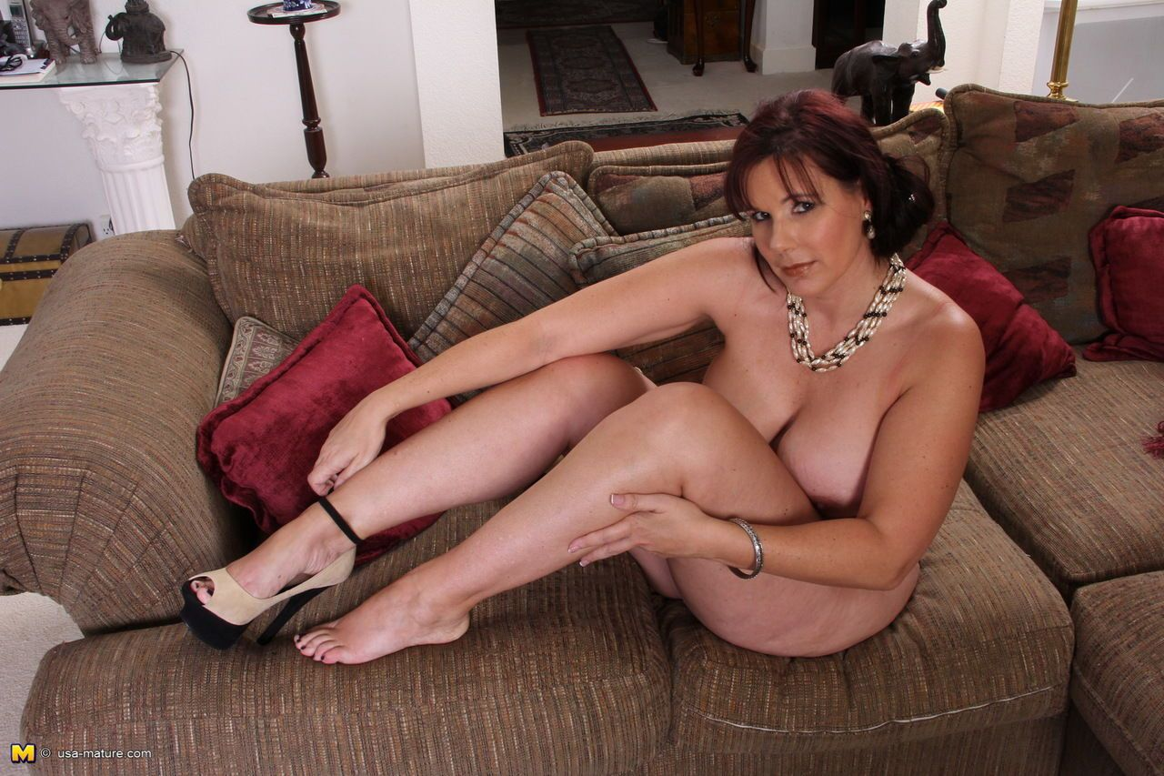 Thick aged woman takes off her dress and black lingerie to pose naked on couch