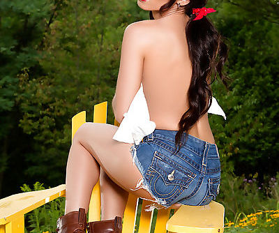 Busty brunette centerfold babe Shay Marie modeling outdoors in boots