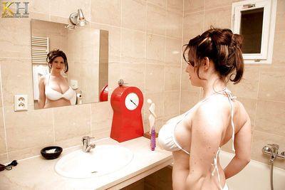 European MILF Karina Hart soaping up her massive tits in the bathtub