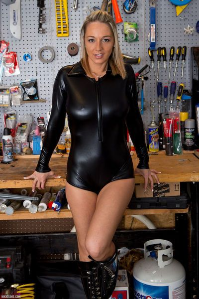 Latex clad Nikki Sims in high heel boots bares her big tits in the workshop