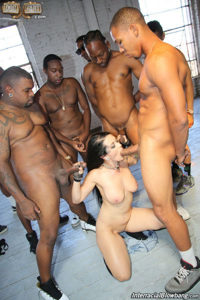 Tattooed brunette Katrina Jade sucks off a group of black men on her knees