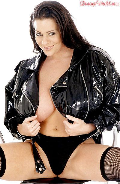 Linsey Dawn McKenzie modeling in latex jacket and black seamed stockings