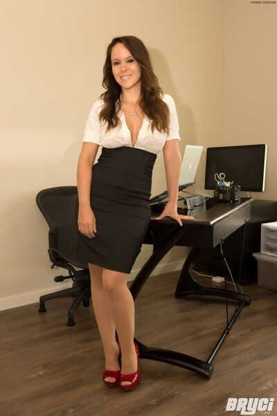 Hot secretary Bryci uncorks her big tits as she strips to red heels in chair