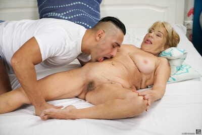Naked granny takes a cumshot on her belly after sex with her toy boy