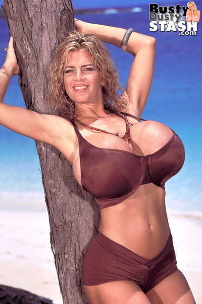 Hot mature lady Busty Dusty sets her giant tits free of her bra near the ocean