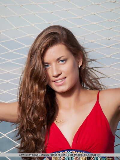Teen glamour model Amanda C posing naked on hammock next to the ocean