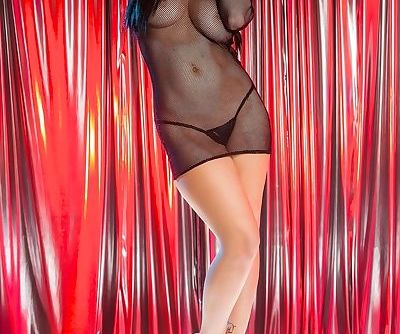 Brunette pornstar Noelle Easton works the stripper pole in see thru dress