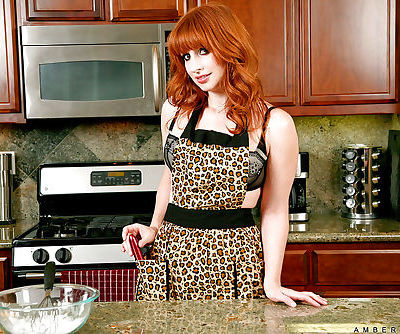 Mature redhead in lingerie Amber Dawn gets naked in the kitchen room